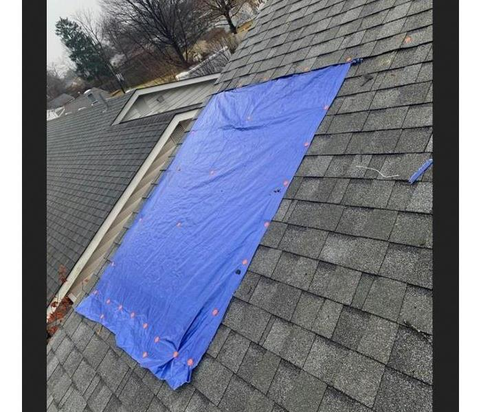 blue tarp on roof after tree went through roof