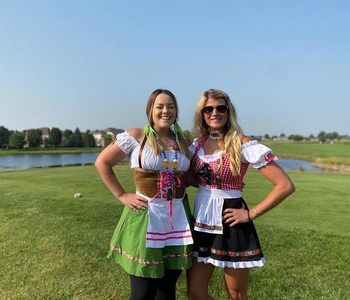 two females standing on golf course in german dresses