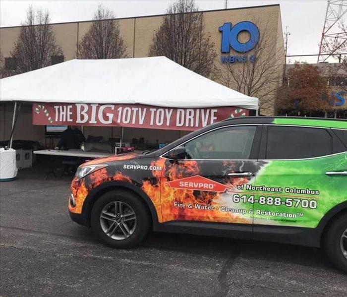 wrapped car in front of white tent with red 10tv big toy drive banner