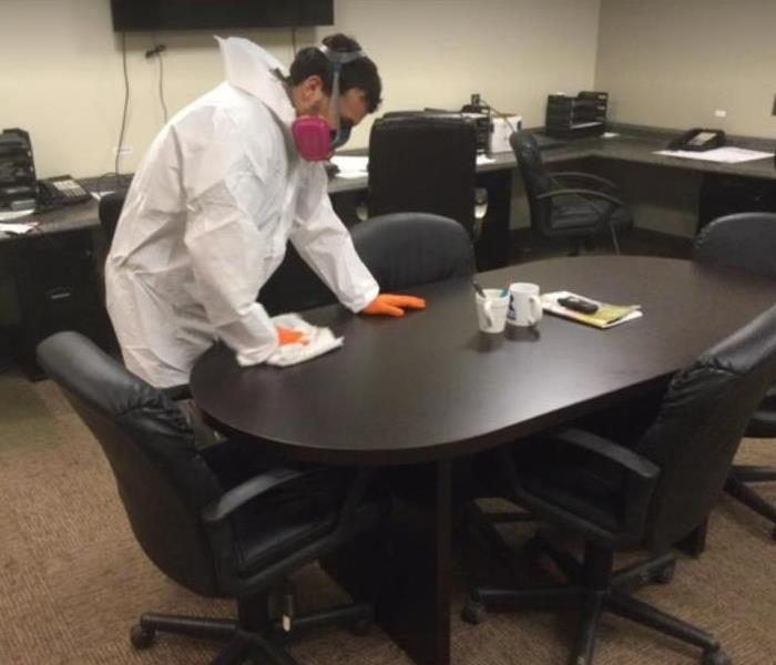technician in hazmat suit wiping down table