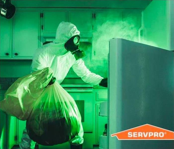 person in white protective gear with mask opening fridge door